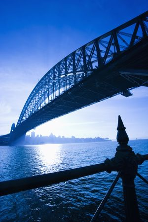 distant: Low angle view of Sydney Harbour Bridge at dusk with harbour and distant Sydney skyline, Australia. Stock Photo