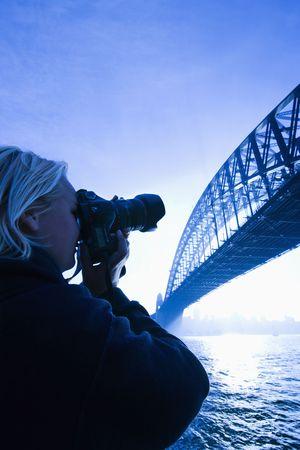 port jackson: Caucasian teenage male photographing Sydney Harbour Bridge at dusk with view of Sydney Harbour, Australia.