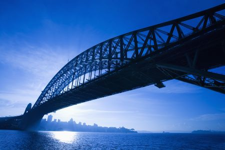 port jackson: Sydney Harbour Bridge at dusk with view of distant skyline and harbour in Sydney, Australia. Stock Photo