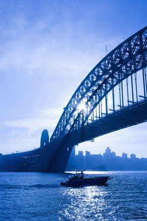 port jackson: Boat under Sydney Harbour Bridge at dusk with view of distant skyline and harbour in Sydney, Australia.