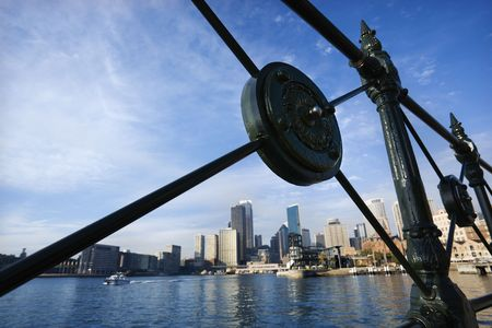 View of Sydney Cove from behind decorative iron railing with city skyline and water in Sydney, Australia. Stock Photo - 2654524