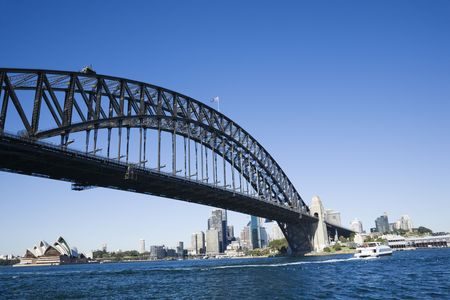 steel arch bridge: Sydney Harbour Bridge with view of downtown buildings and Sydney Opera House in Australia. Stock Photo