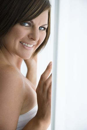 Caucasian mid adult brunette woman near window smiling at viewer. Stock Photo - 2655327