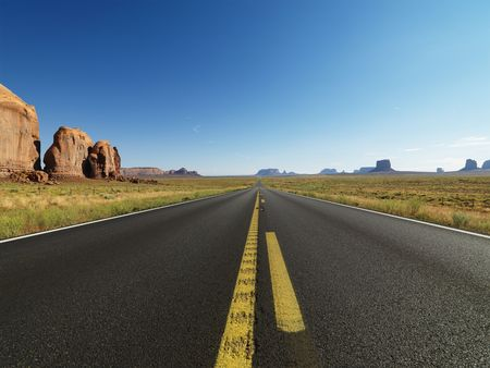 butte: Open highway in scenic desert landscape with distant mountains and butte land formations.