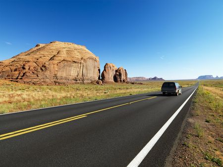 SUV on highway in scenic desert landscape with butte land formation.