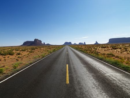 Open road in scenic desert landscape with distant mountains and mesas. photo