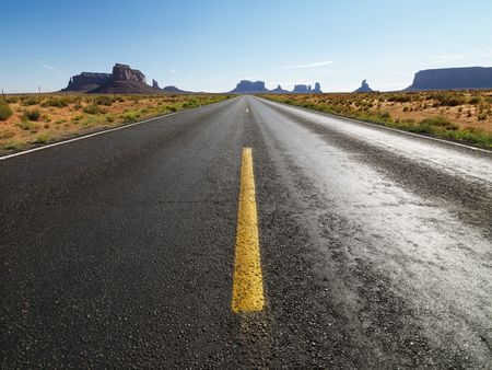 mesas: Open highway in scenic desert landscape with distant mountains and mesas.