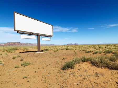 Blank billboard in middle of desert landscape with distant mountains.
