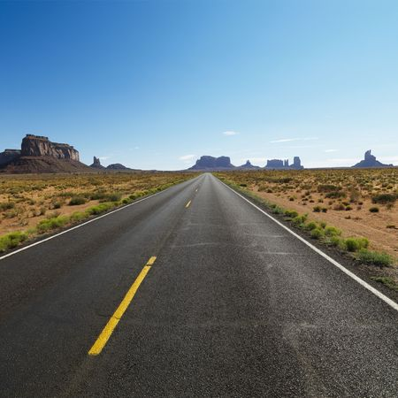 mesas: Open road in scenic desert landscape with distant mountains and mesas. Stock Photo