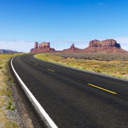 mesa: Curve in road in scenic desert road with mesa land formations and mountains.