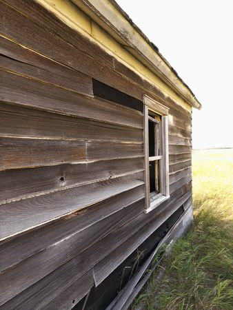 dilapidated: Side of abandoned wooden dilapidated house. Stock Photo