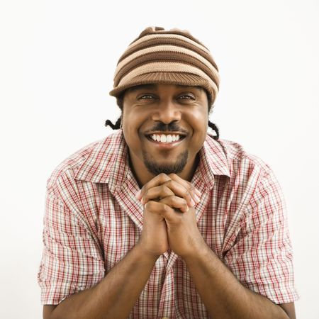 African-American mid-adult man wearing hat and smiling at viewer with hands together. photo