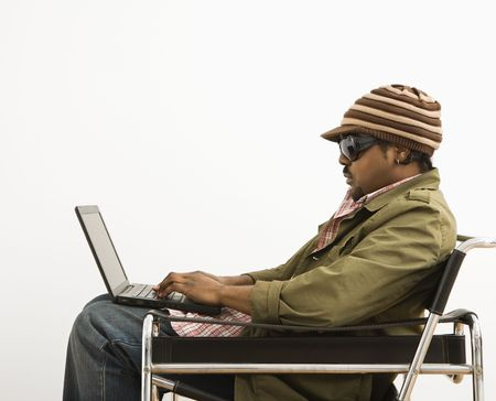 Side view of African-American mid-adult man wearing hat and typing on laptop computer. Stock Photo - 2655019