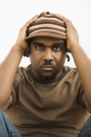 African-American mid-adult man holding head wearing hat looking at viewer. photo