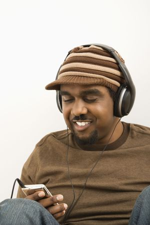 African-American mid-adult man wearing hat and listening to mp3 player. photo