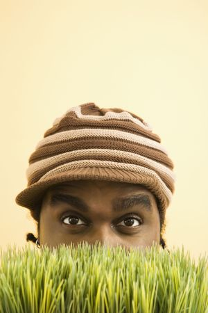 African-American mid-adult man wearing knit hat with brim peeking at viewer from behind grass. photo