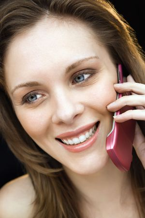 Close up portrait of young adult female talking on mobile phone and smiling. photo