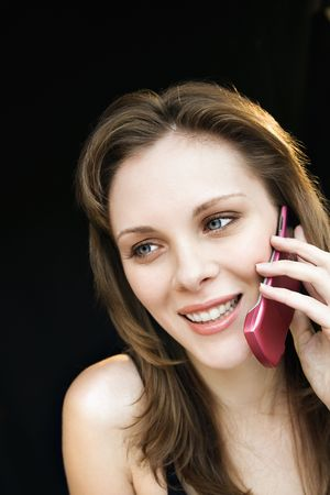Close up portrait of young adult female talking on cell phone and smiling. photo