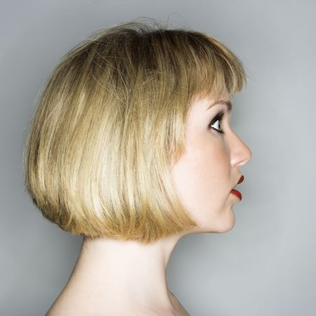 Profile portrait of young blonde caucasian woman who looks surprised.