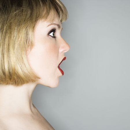 Profile portrait of young blonde caucasian woman whos mouth is open in shock. photo
