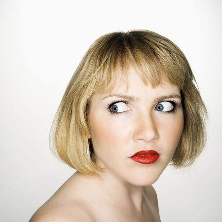Portrait of young blonde caucasian woman who has suspicious expression. photo