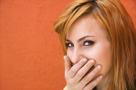 Young redheaded woman laughing with hand over mouth. Stock Photo - 3548298