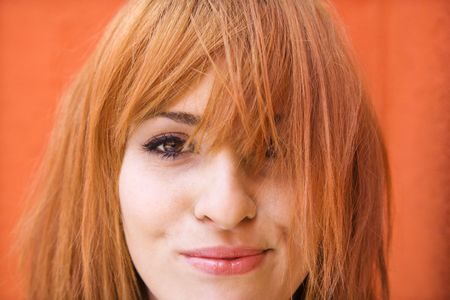 Young redheaded woman looking at viewer with funny expression. photo