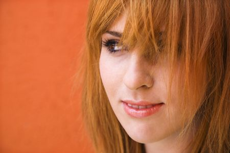 redheaded: Close-up portrait of smiling young redheaded female looking mischievious. Stock Photo