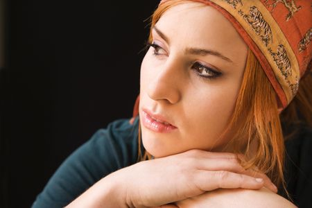 Young redheaded woman wearing cap looking off to side. photo
