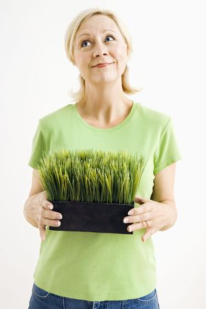 Portrait of attractive adult woman holding pot of grass and looking up. photo
