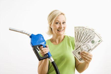 bomba de gasolina: Retrato de adultos sonriente rubia mujer explotaci�n de gas boquilla y un mont�n de dinero.  Foto de archivo