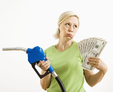 irked: Portrait of distressed adult blonde woman holding gas nozzle and lots of money.