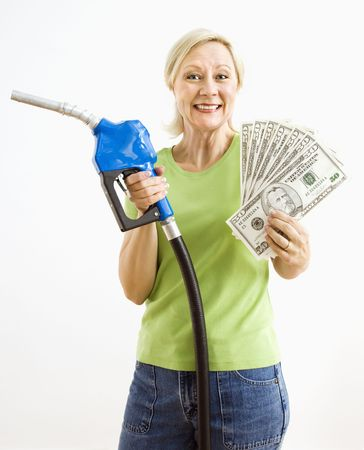 Portrait of smiling adult blonde woman holding gas nozzle and lots of money. photo