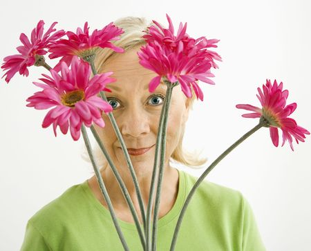Portrait of smiling adult blonde woman looking through bouquet of pink flowers at viewer. Stock Photo - 3557456