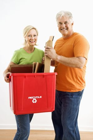Man and woman smiling while holding recycling bin. Stock Photo - 3557470
