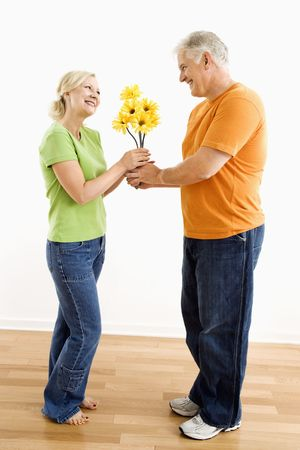 Middle-aged man giving woman bouquet of yellow flowers. Stock Photo - 3557463