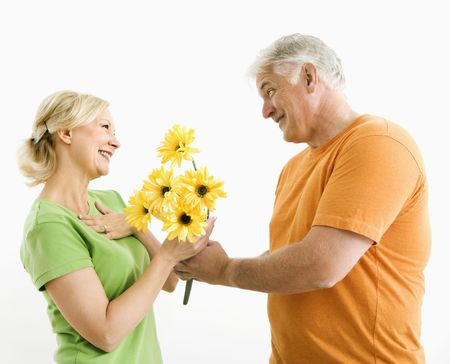 Middle-aged man giving woman bouquet of yellow flowers. Stock Photo - 3557438