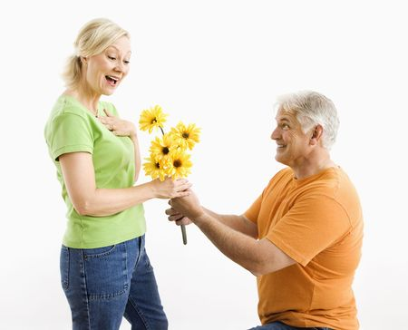 courting: Middle-aged man on bended knee giving woman bouquet of yellow flowers.