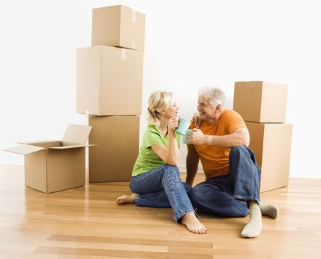 Middle-aged couple sitting on floor among cardboard moving boxes drinking coffee. photo