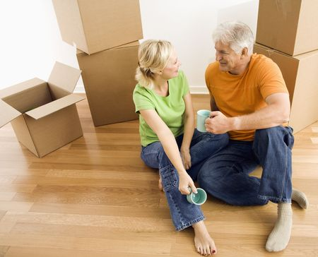 Middle-aged couple sitting on floor among cardboard moving boxes drinking coffee. Stock Photo - 3557512