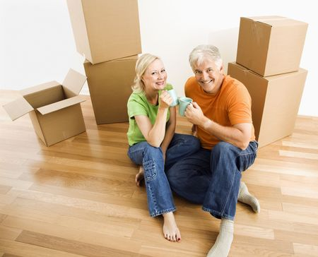 Middle-aged couple sitting on floor among cardboard moving boxes with coffee. Stock Photo - 3557487