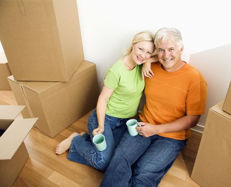 Middle-aged couple sitting on floor among cardboard moving boxes with coffee. photo