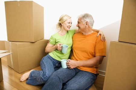 Couple sitting on floor among cardboard moving boxes drinking coffee. photo