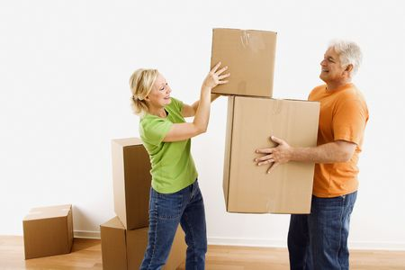 Middle-aged man holding cardboard moving boxes while woman places one on stack. photo