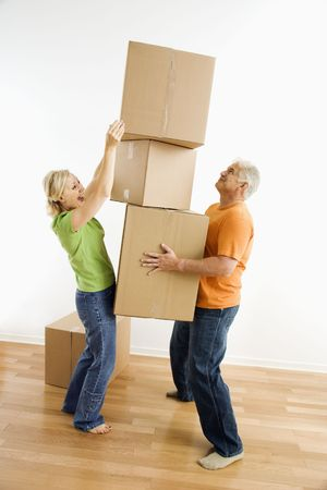 Middle-aged man holding stack of cardboard moving boxes while woman places another one on. Stock Photo - 3557418