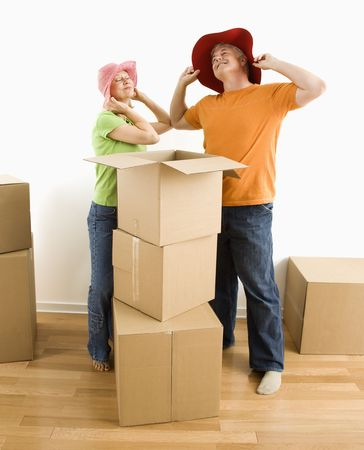 Middle-aged couple trying on silly hats while packing or unpacking moving boxes. Stock Photo - 3557420