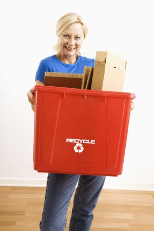 Portrait of smiling adult blonde woman holding recycling bin full of cardboard. photo