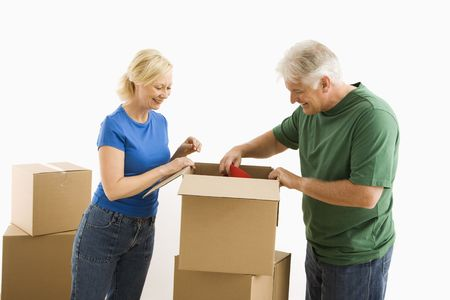 Middle-aged couple packing or unpacking moving boxes. photo