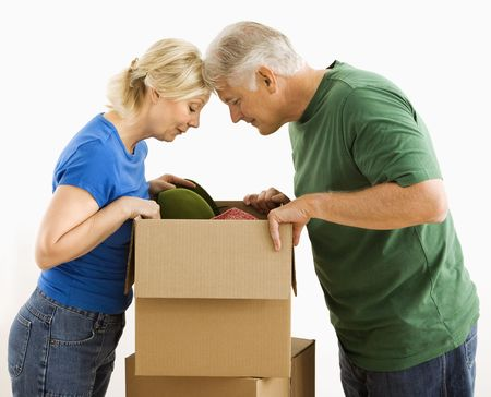 Middle-aged couple looking through cardboard box. photo