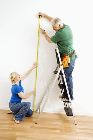 Middle-aged couple measuring wall with tape. photo